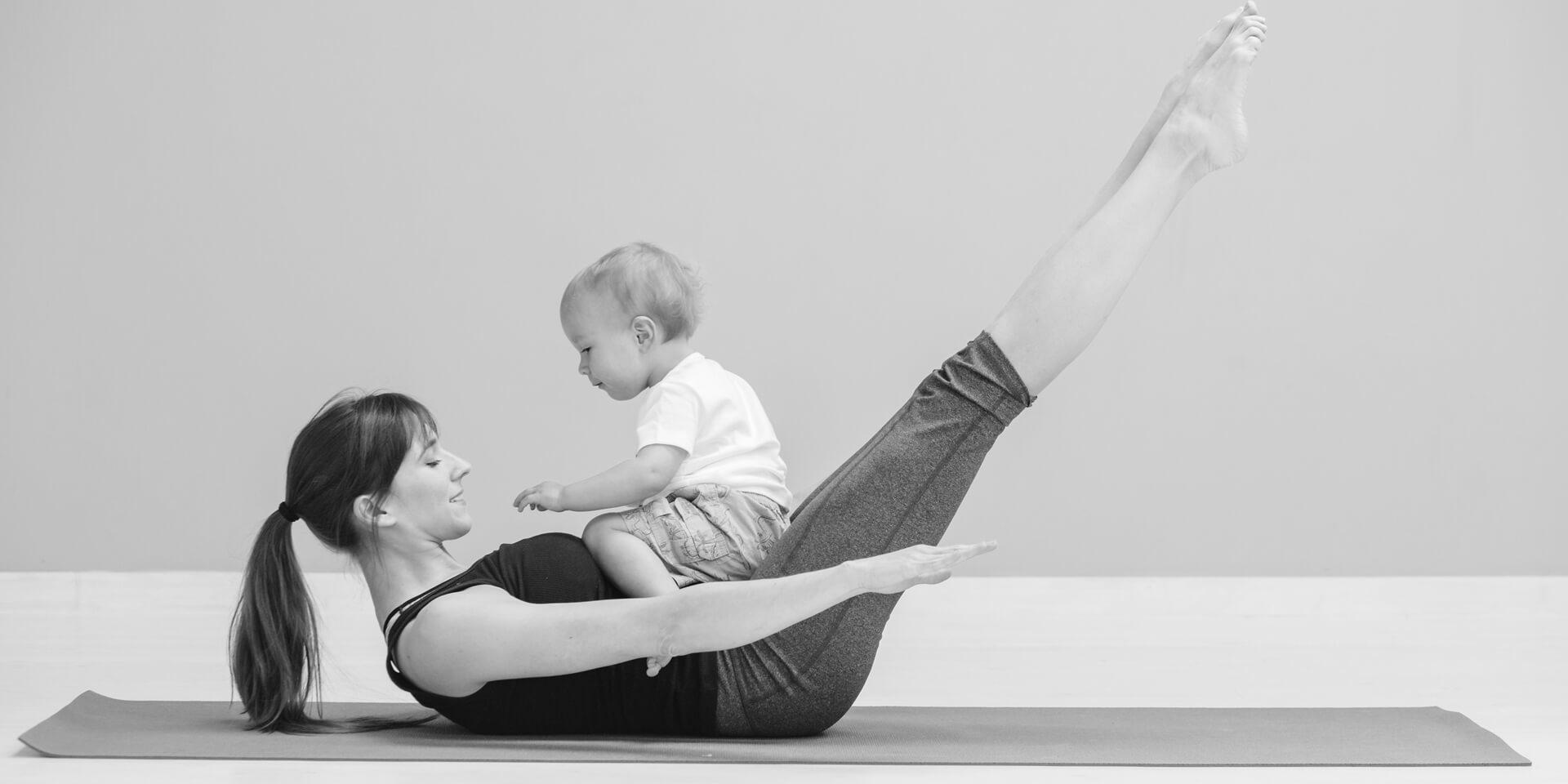 Frau mit Kind macht Fitnessübung für Bauchmuskeln