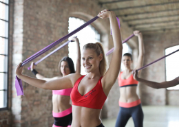 Frauen trainieren gemeinsam in der Gruppe Pilates mit Rubberband