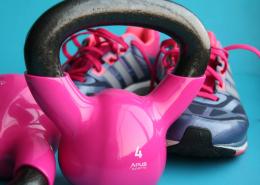 Sportschuhe von Frauen mit zwei pinken Kettlebells