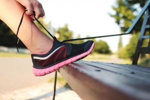 Frau schnürt sich den Sportschuh um outdoor zu trainieren