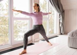Frau trainiert zuhause im Schlafzimmer auf Yoga Matte